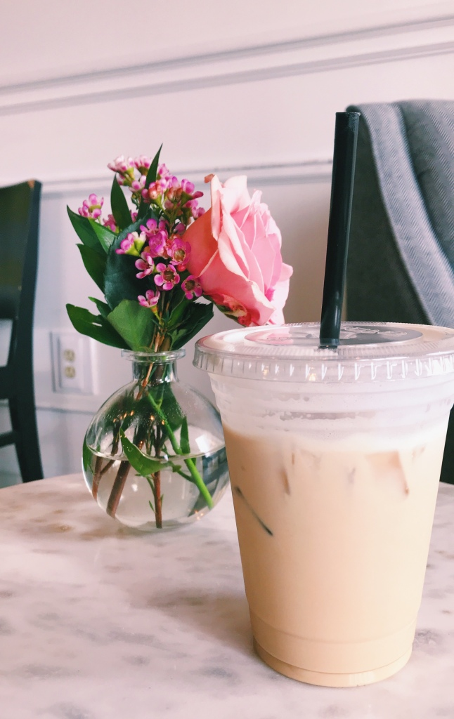 Photo of iced coffee from Cavu Coffee. It is sitting on a marble table next to a vase of flowers