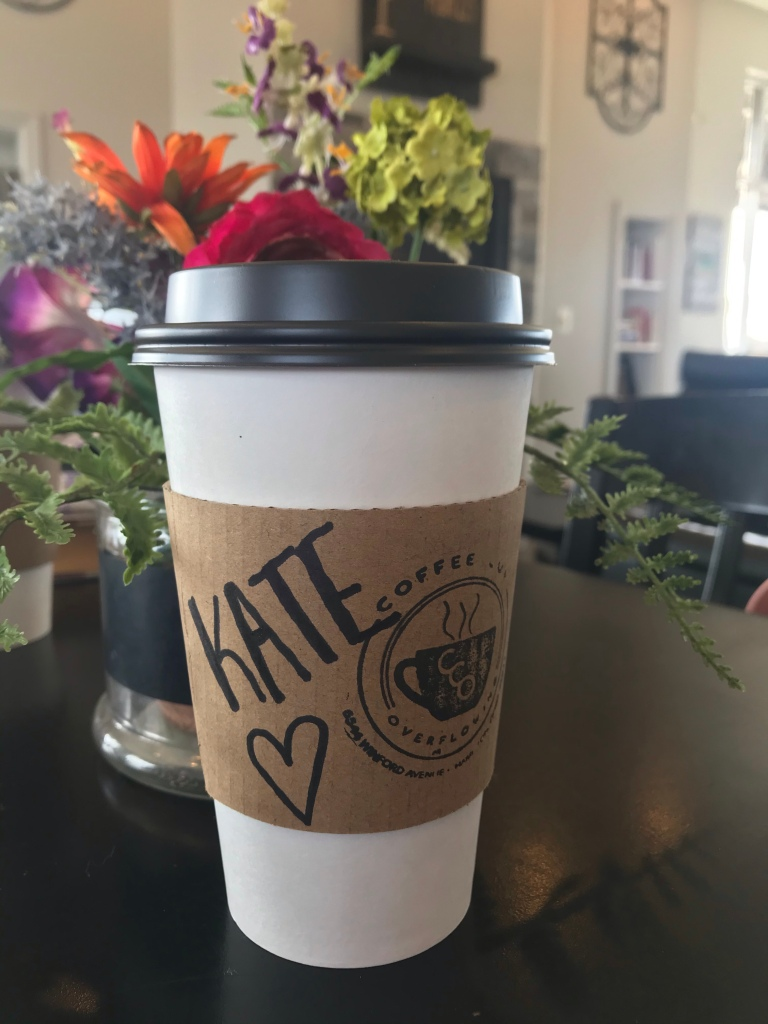 "A coffee cup that says ""Coffee Cup Overflowing"" and has the name, ""Kate"" written with a marker. It is sitting next to a vase of flowers"