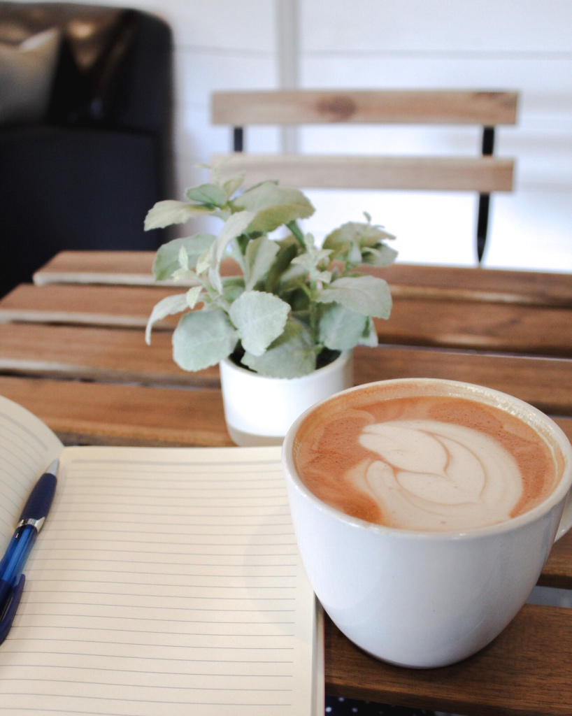 Photo of a latte in a mug on top of a wooden table. It is next to a plant and a journal.